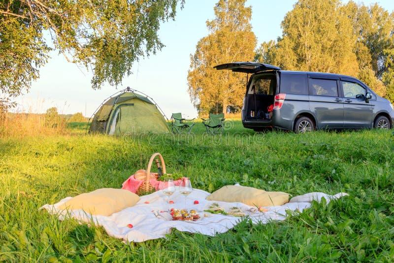Picknickdatum i skog, tält och fällstolar, grå minibuss med den öppna dörren, filt, vide- korg, vinexponeringsglas, mellanmål, fr arkivfoton