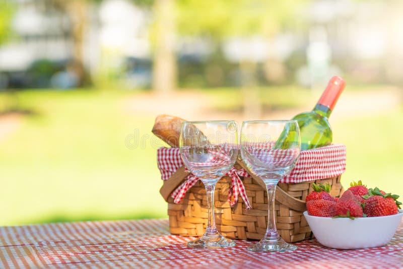Picknickkorb kariert mit einem Tischdeckenwein, Stangenbrot, Erdbeere, Gläser, Fahne lizenzfreies stockfoto