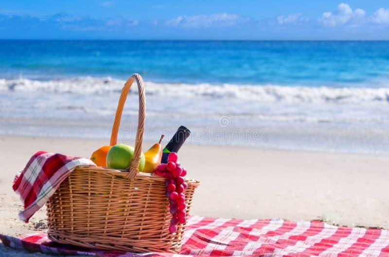 Picknickkorb mit Früchten durch den Ozean lizenzfreie stockfotografie