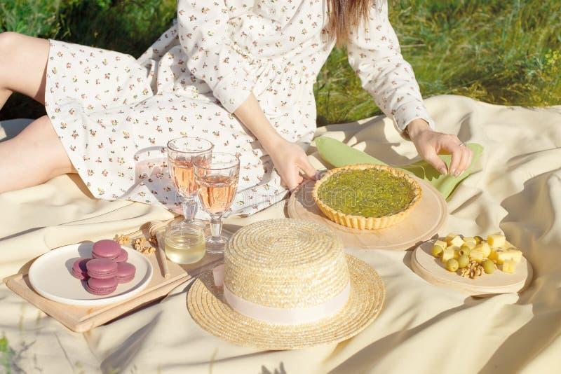 Picknickkorg med frukt och bageri p? den r?da torkduken i genomskinliga exponeringsglas f?r gardenmacaroonbageri av drinken p? et fotografering för bildbyråer