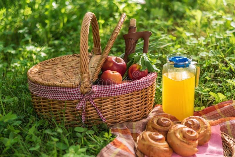 Picknickkorg med vinfrukt och andra produkter på en naturlig träbakgrund Sommar vilar Campa Picknick i natur arkivfoton