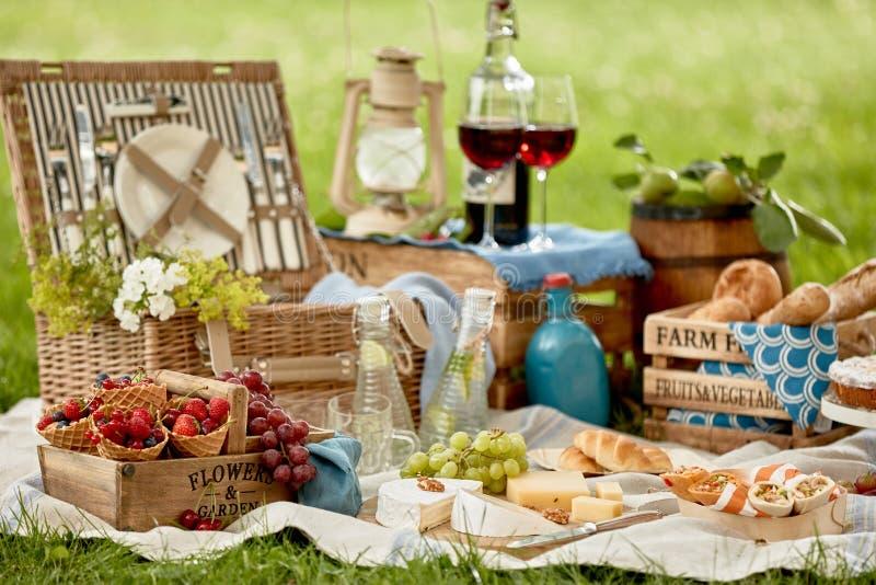 Picknickkorg som omges av läcker ny mat arkivbild