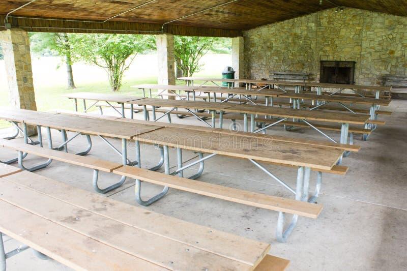 Picknicklijsten in een schuilplaatshuis stock fotografie