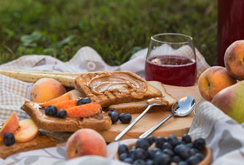 Picknicklunchmål parkerar utomhus matbegrepp, closeupen av picknickkorgen med drinkar, mat och blommor på gräset royaltyfri bild