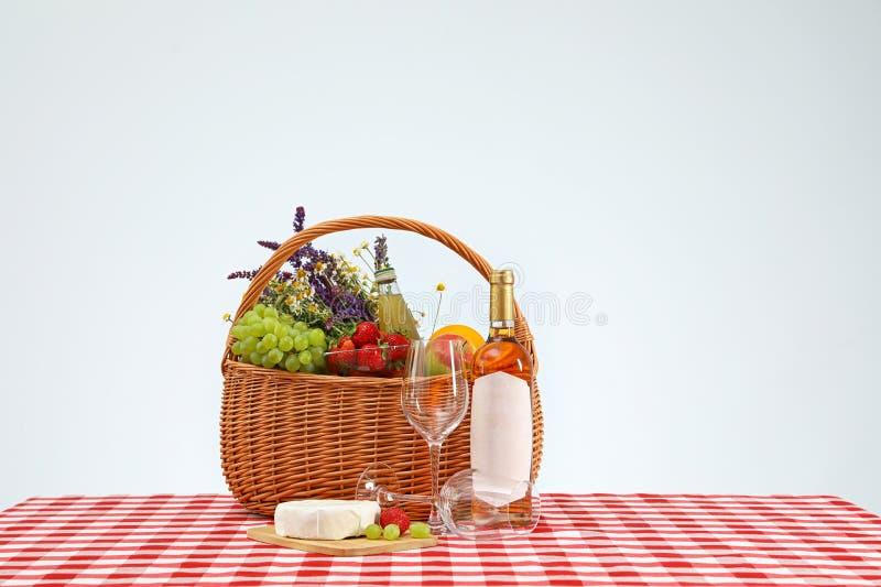 Picknickmand met wijn en producten op geruit tafelkleed royalty-vrije stock afbeeldingen