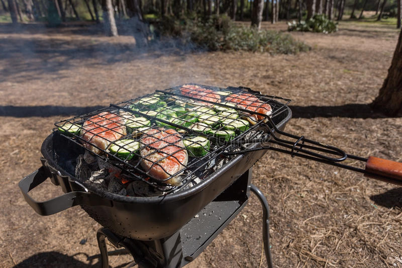 Picknickmatlagning utomhus med ett galler arkivbilder