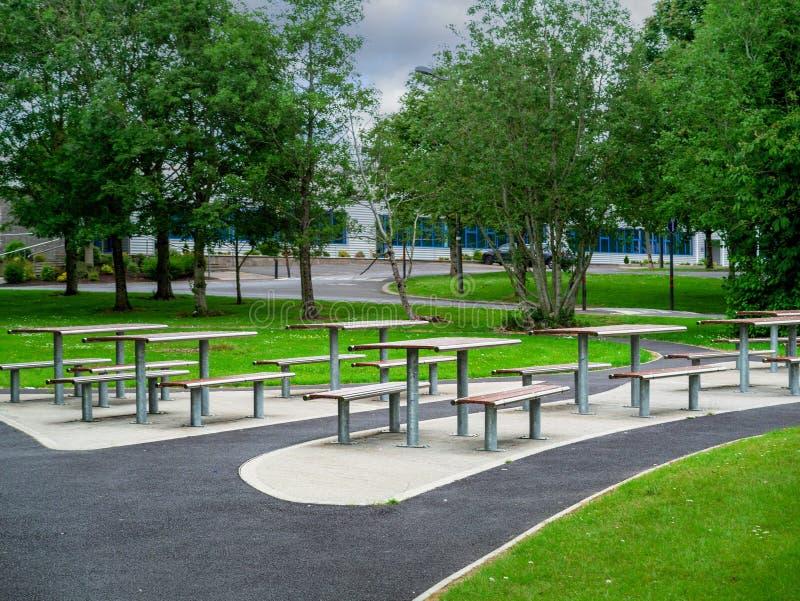 Picknickområde med kontorsbyggnad för personalavbrott utomhus Modern metalltabell och plats Gr?na tr?d och gr?nt gr?s royaltyfria bilder
