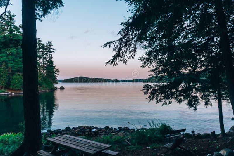 Picknicktisch durch einen See stockfotografie
