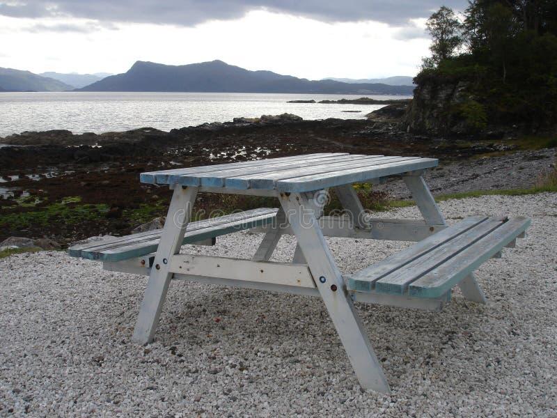 Picknicktisch durch Wasser lizenzfreie stockbilder