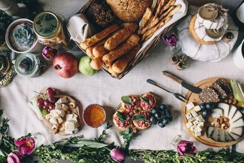 Picknicktisch: geschnittener Ziegenkäse, dorblu, Brot, Trauben, Birne, Haselnüsse stockfoto
