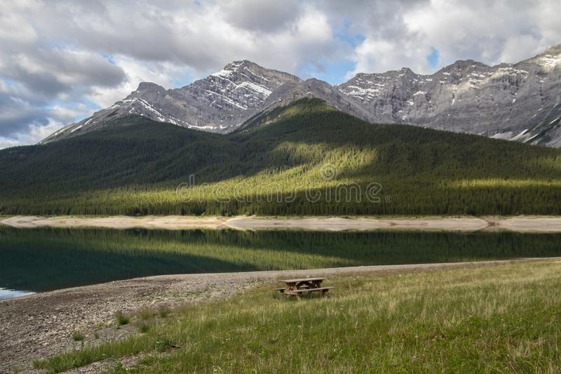 Picknicktisch nahe bei dem Wasser mit Bergen im Abstand stockfoto
