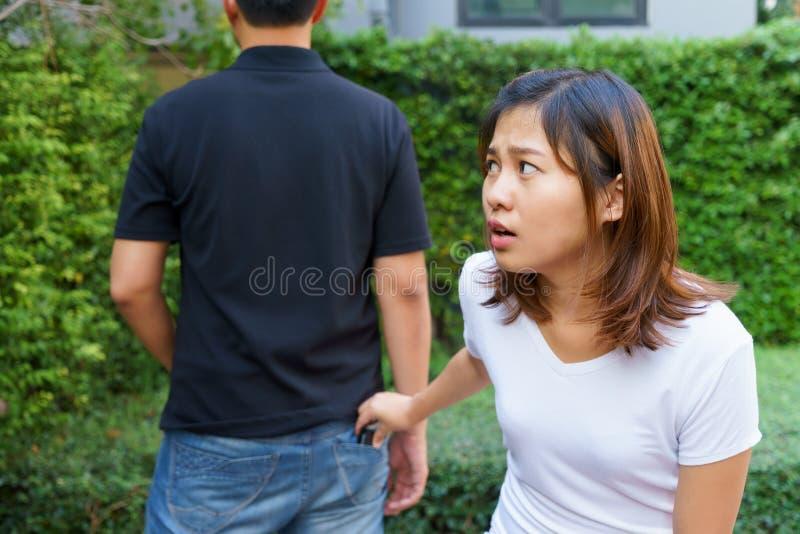 Pickpocket féminin volant un portefeuille par derrière la poche sur des jeans images stock