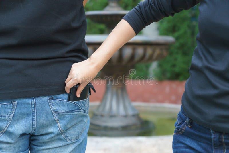 Pickpocket féminin volant un portefeuille par derrière la poche sur des jeans photographie stock