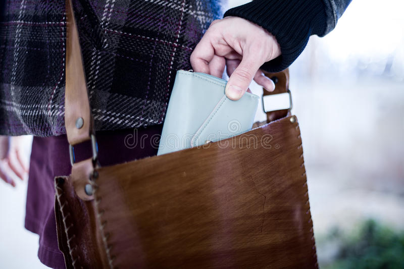 Pickpocket. Stealing a Wallet from a Leather Bag stock photography