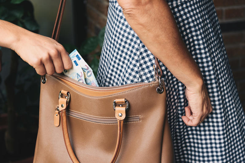 Pickpocket thief is stealing money stock photo