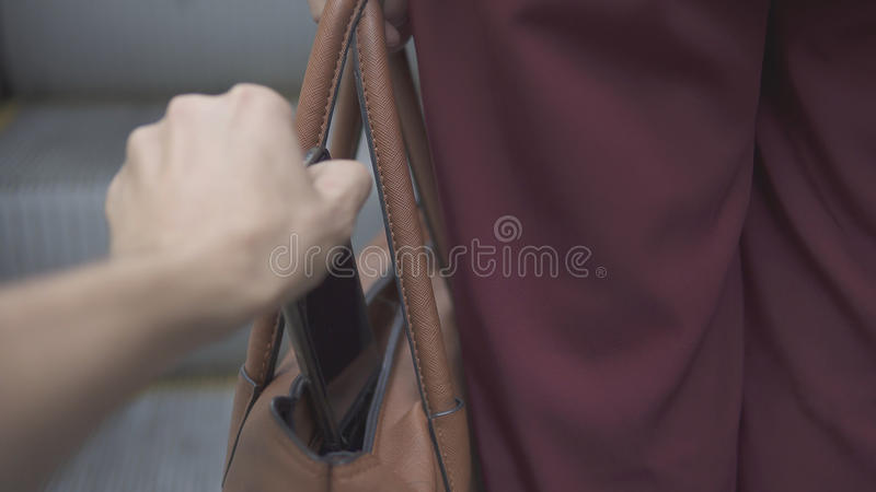 Pickpocket thief is stealing smartphone from orange handbag. stock photography