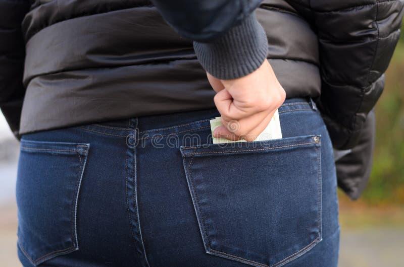 Pickpocket volant l'argent liquide d'une femme photo libre de droits
