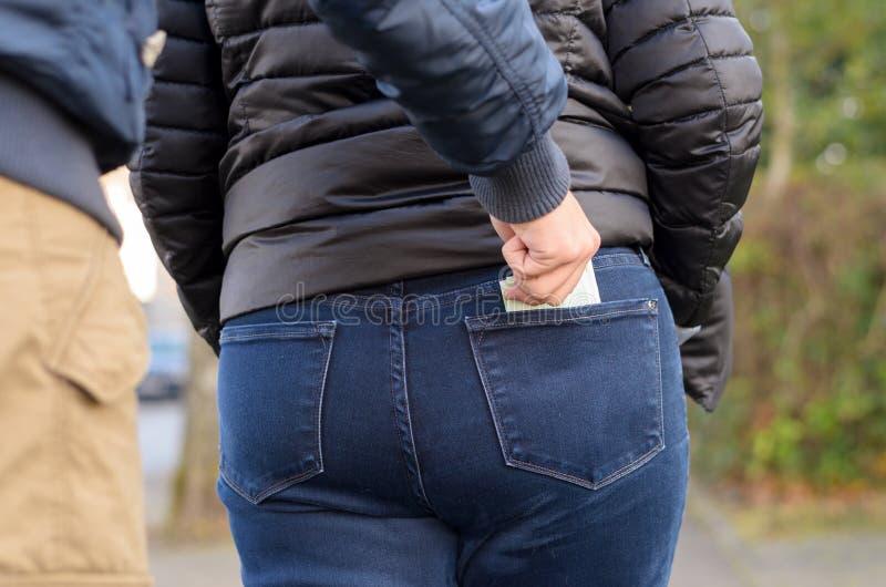 Pickpocket volant l'argent liquide d'une femme photos libres de droits