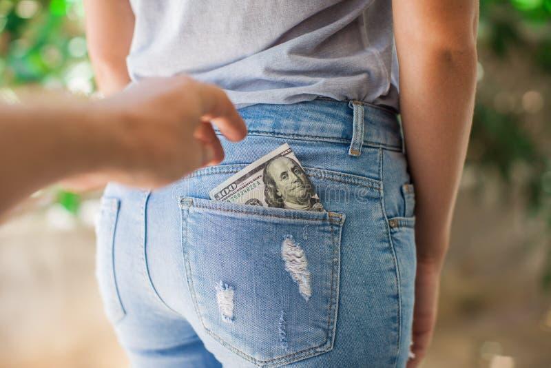 Pickpocket volant l'argent liquide d'une poche de dos de femme photos libres de droits
