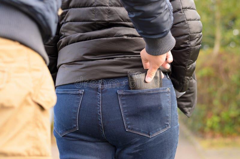 Pickpocket volant une bourse d'une femme photo libre de droits