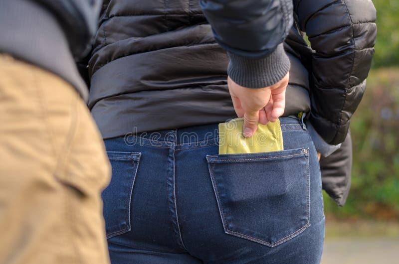 Pickpocket volant une bourse d'une femme images libres de droits
