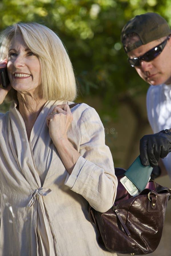 Pickpocketer поднимает бумажник от сумки женщины стоковые фотографии rf