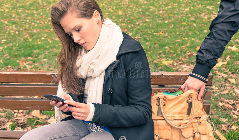 Pickpocketing from the bag of a young woman in a park stock photography