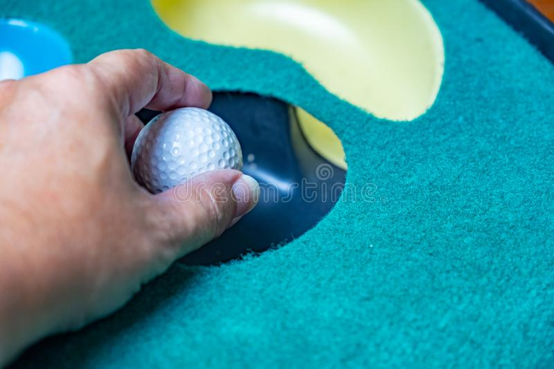 Pickup piłka golfowa na kładzenie macie obrazy stock