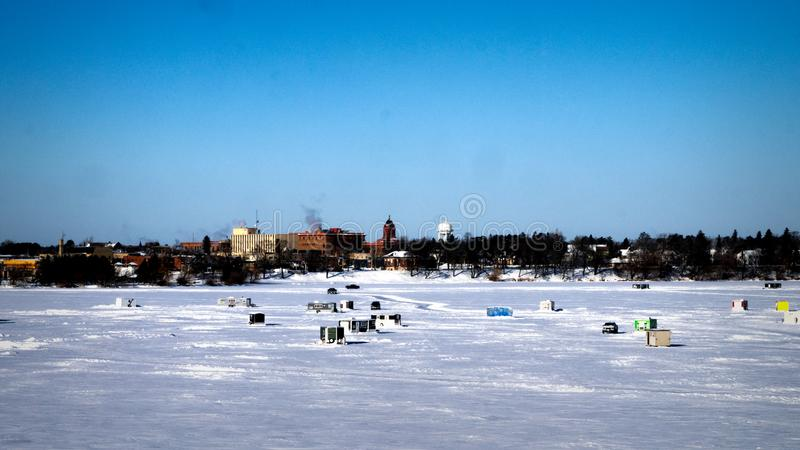 Pickup Trucks Drive Onto Frozen Lake With Winter Fish Houses in Background on a Sunny Morning stock images