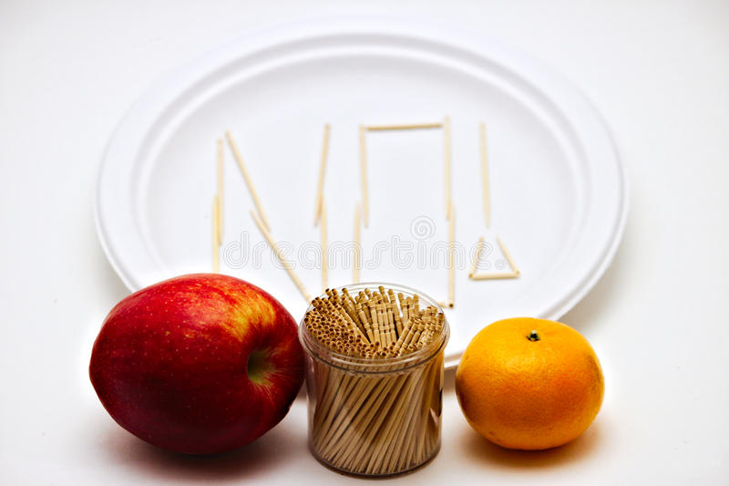 Picky Eater - Apple and Orange. Picky Eater - Apple, Orange. Concept of a picky eater is represented by toothpicks spelling out the word `NO` on a plate in stock photo