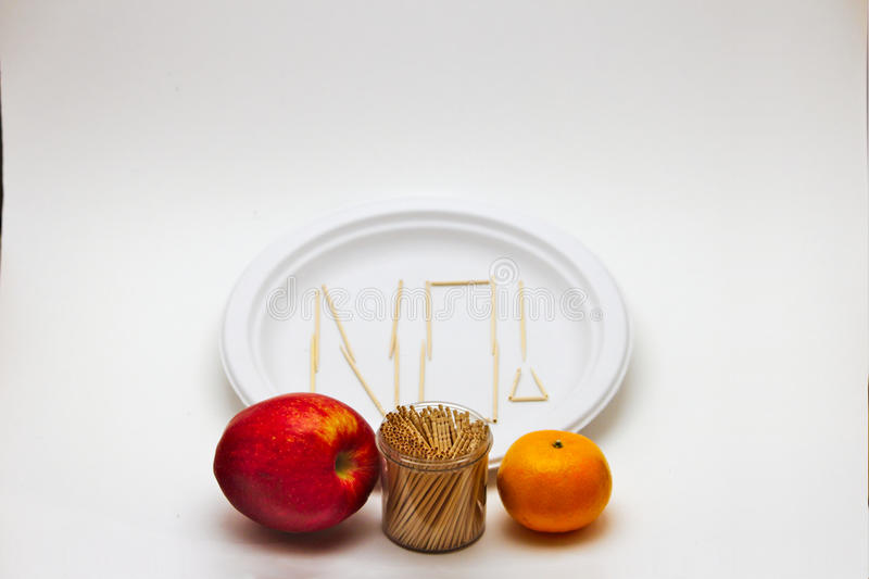 Picky Eater - Apple and Orange. Concept of a picky eater is represented by toothpicks spelling out the word `NO` on a plate in rejection to the raw ingredients stock image