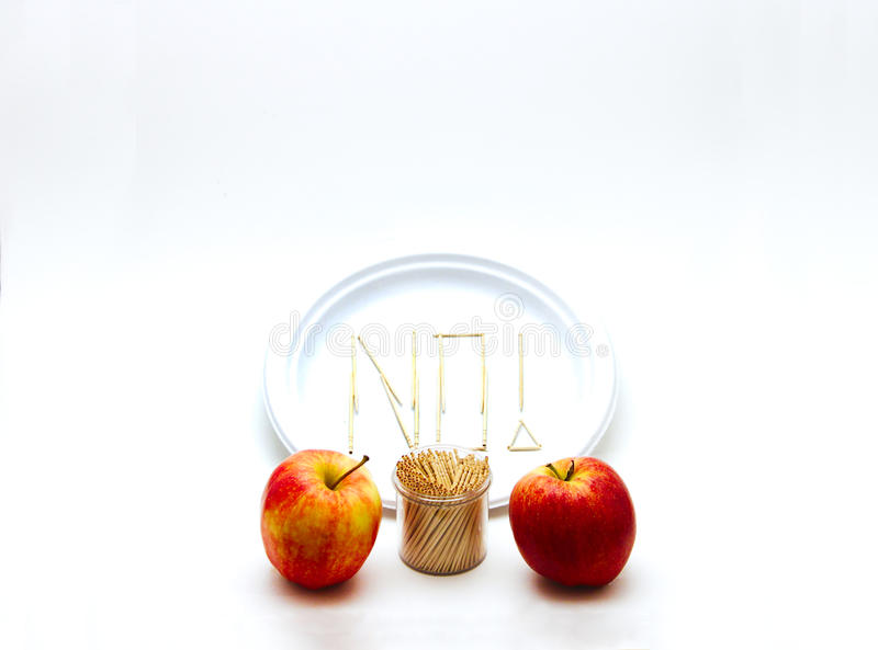 Picky Eater - Apples Small. Concept of a picky eater is represented by toothpicks spelling out the word `NO` on a plate in rejection to the raw ingredients royalty free stock images