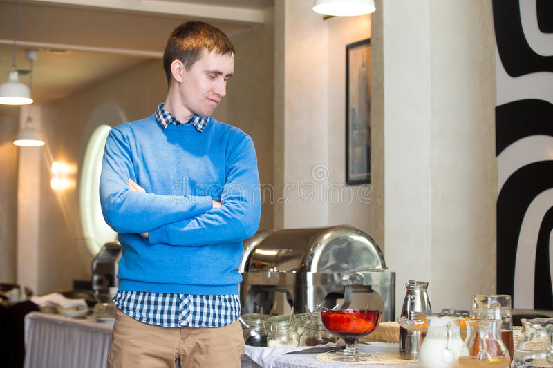 Picky eater at breakfast. Portrait of young man at self-catering breakfast in hotel restaurant, picky eater fed-up with food, showing disappointment on his face royalty free stock photo