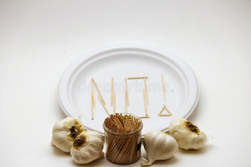 Picky Eater - Garlic. Concept of a picky eater is represented by toothpicks spelling out the word `NO` on a plate in rejection to the raw ingredients displayed royalty free stock photography