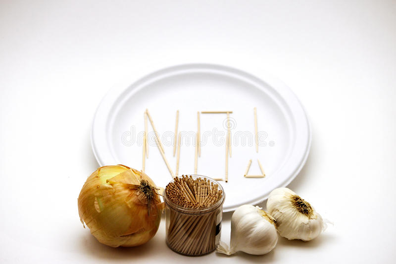 Picky Eater - Garlic and Onions. Picky Eater - Garlic, Onions. Concept of a picky eater is represented by toothpicks spelling out the word `NO` on a plate in royalty free stock photography