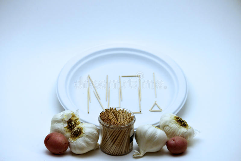 Picky Eater - Garlic and Potato. Concept of a picky eater is represented by toothpicks spelling out the word `NO` on a plate in rejection to the raw stock photography