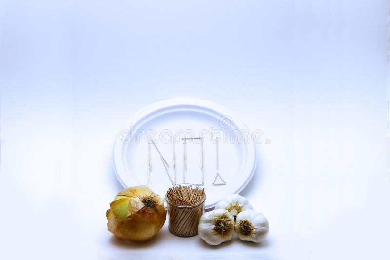 Picky Eater - Garlic and Potato. Concept of a picky eater is represented by toothpicks spelling out the word `NO` on a plate in rejection to the raw stock photos