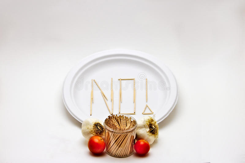 Picky Eater - Garlic and Tomato. Picky Eater - Apple, Orange. Concept of a picky eater is represented by toothpicks spelling out the word `NO` on a plate in royalty free stock photo