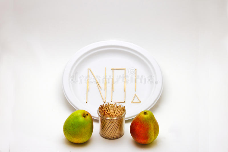 Picky Eater - Pears. Concept of a picky eater is represented by toothpicks spelling out the word `NO` on a plate in rejection to the raw ingredients displayed in stock photo