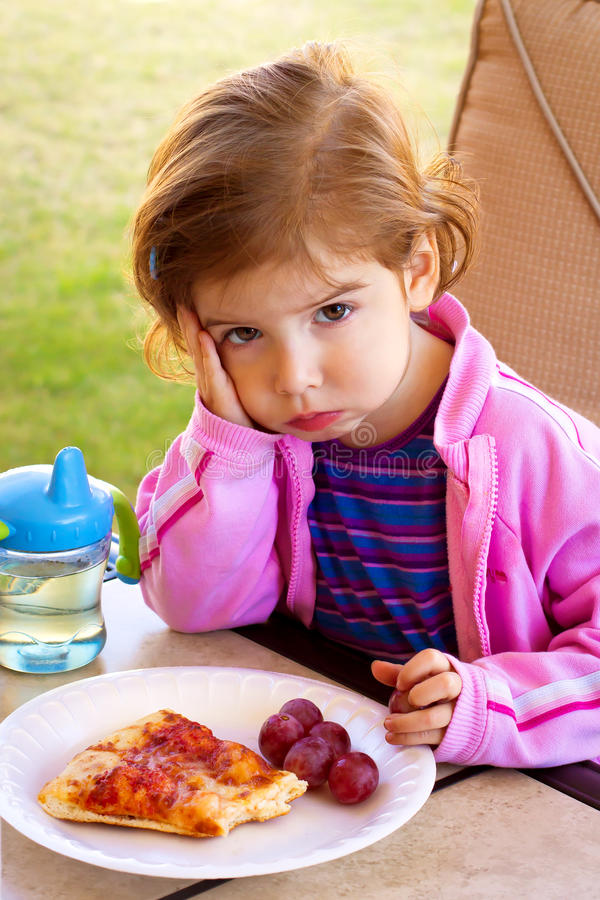 Picky Eater. A toddler girl sits pouting and glaring in front of a plate of partially eaten food royalty free stock image