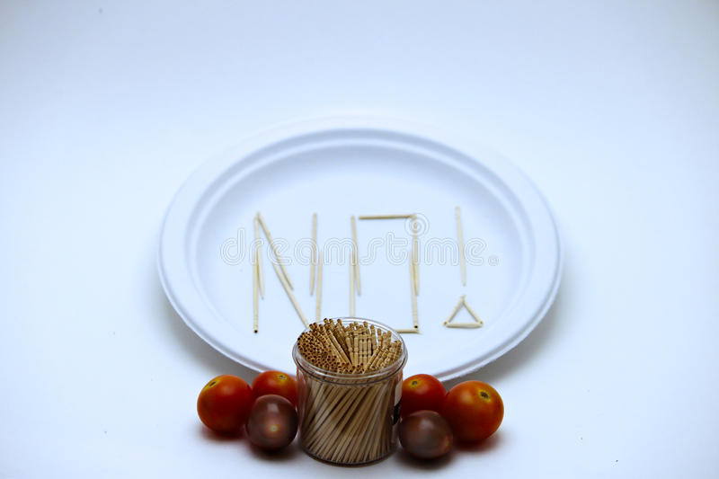 Picky Eater - Tomatoes. Picky Eater - Cherry Tomatoes. Concept of a picky eater is represented by toothpicks spelling out the word `NO` on a plate in rejection stock image