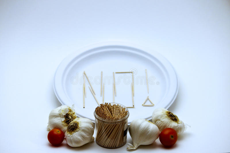 Picky Eater - Tomatoes and Garlic. Picky Eater - Tomatoes, Garlic. Concept of a picky eater is represented by toothpicks spelling out the word `NO` on a plate in stock image