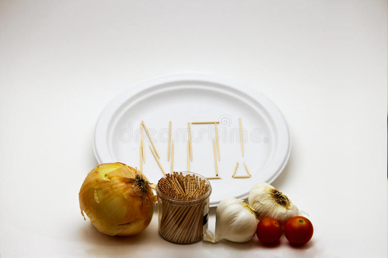 Picky Eater - Tomatoes, Onions and Garlic. Concept of a picky eater is represented by toothpicks spelling out the word `NO` on a plate in rejection to the raw stock photos