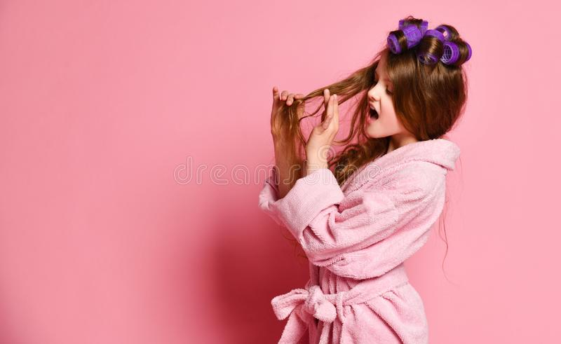 Picky young lady or teen girl in spa salon is frightened with her hair style condition or something stuck in her hair. Beauty concept on pink background royalty free stock image