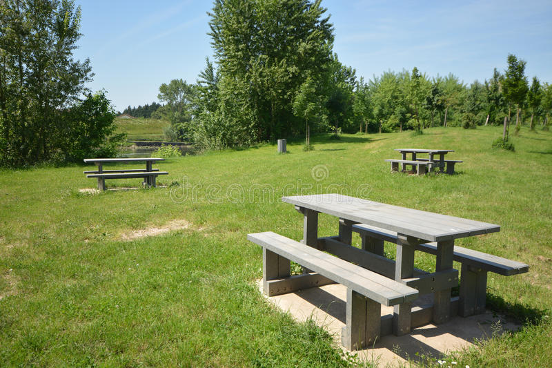 Picnic area in France. A picnic area with wooden tables and wooden bench seats to have a leisurely meal and glass of best French wine on a lovely sunny day in royalty free stock images