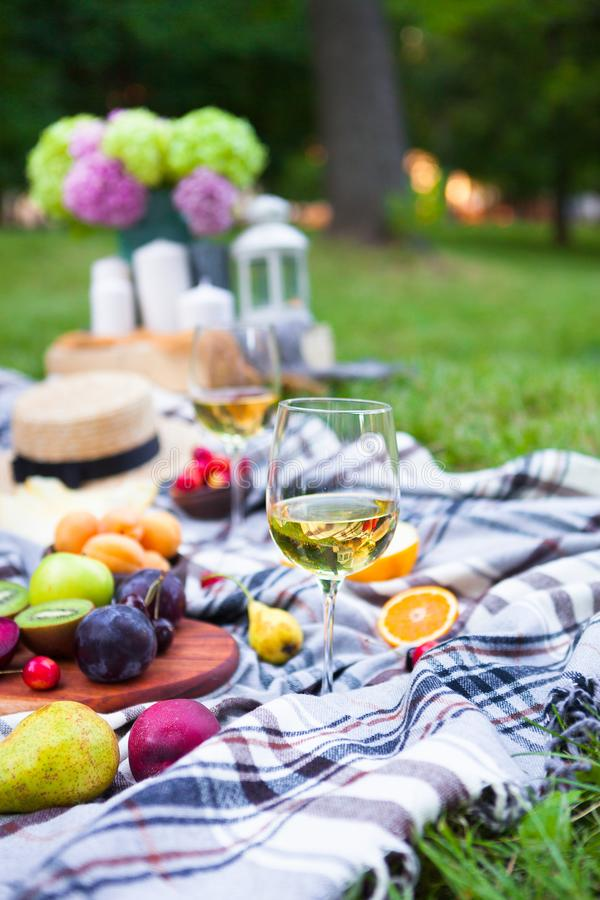 Picnic background with white wine and summer fruits on green grass, summertime party stock photo