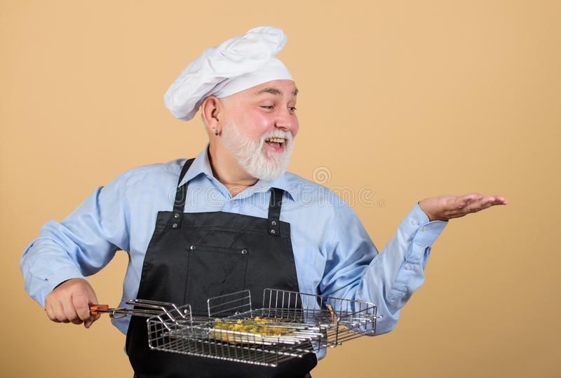 Picnic and barbecue concept. Bbq concept. Barbeque and smoked dish. Grilling food. Mature bearded chef hold grilling stock photos