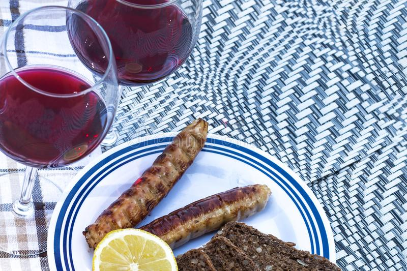 Picnic, barbecue in nature. Red wine, grilled sausages, vegetables and bread on a beautiful tablecloth royalty free stock photos