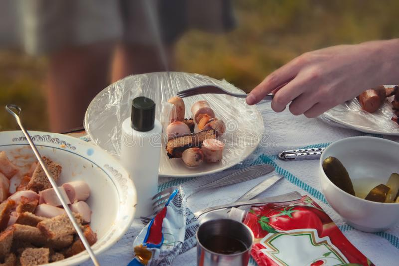 Picnic barbecue in outdoors with sausages, fried bread and ketchup stock photos
