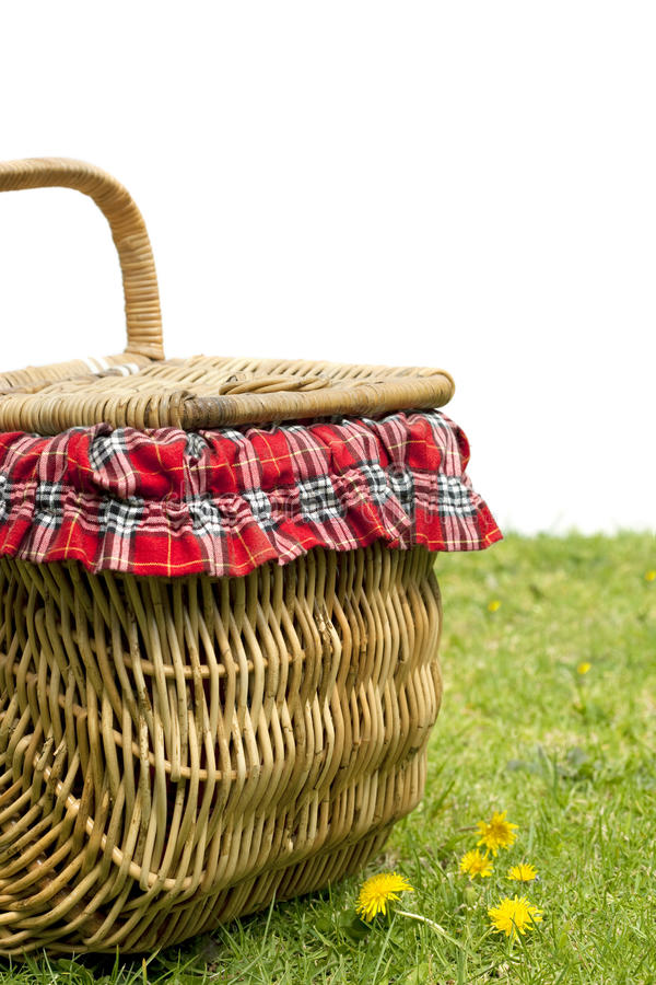 Picnic Basket. On green grass, over white background. Lots of copy space royalty free stock photo